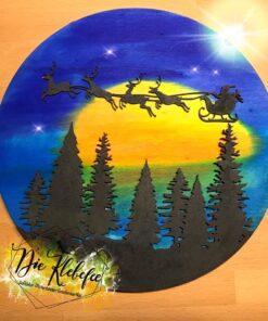 Weihnachtliche Holzscheibe mit einem Wald und Rentierschlitten